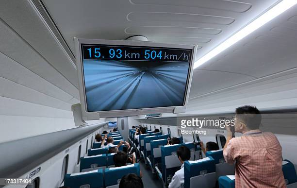 A photographer works near a monitor showing a live view from the front of the train and the current speed inside the L0 series magneticlevitation...
