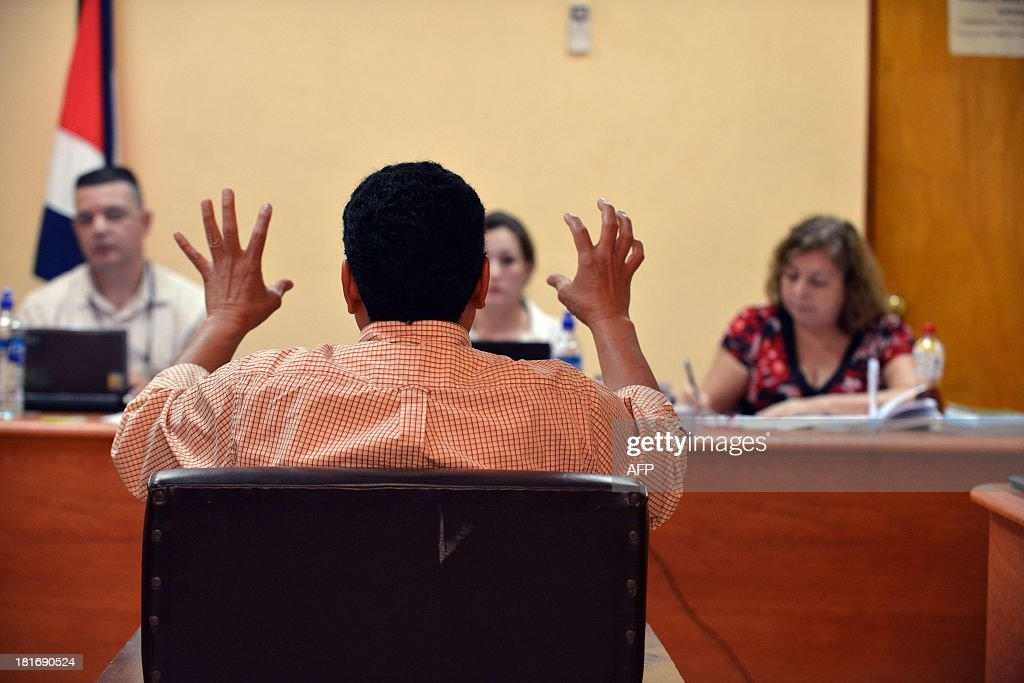 AFP photographer Yuri Cortez (back to the camera) explains in court in Puntarenas, 77 km southwest of San Jose how he was shot at by hired bodyguards during the marriage of Brazilian top model Gisele Bundchen and U.S. football player Tom Brady in Playa Santa Teresa in Puntarenas in 2004. AFP PHOTO/EZEQUIEL BECERRA