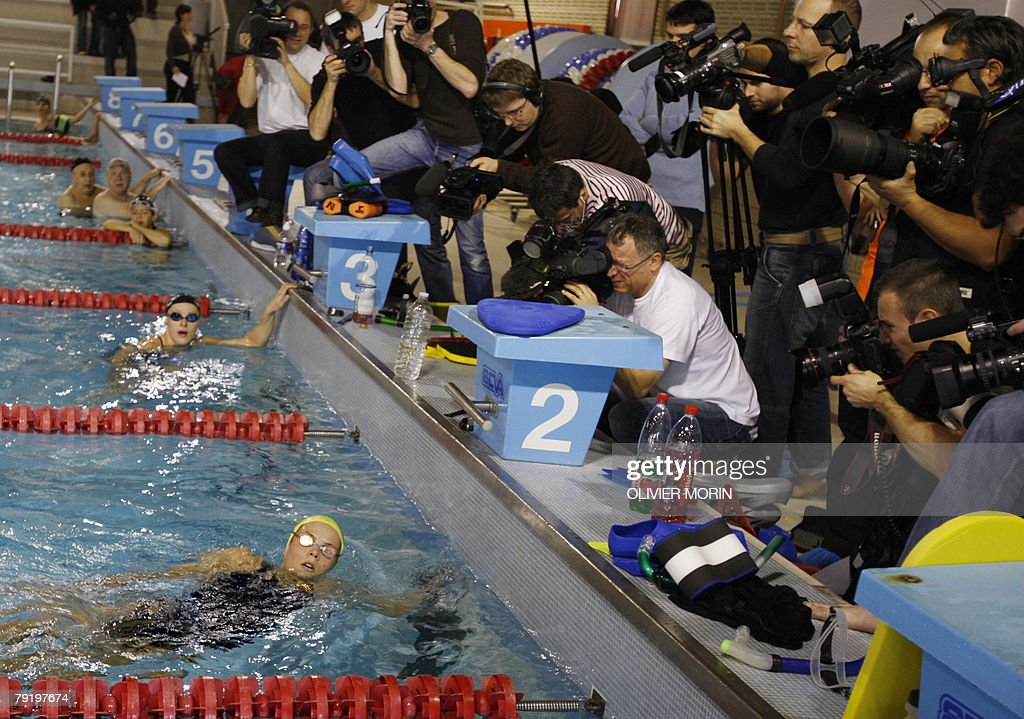 Photographers and cameramen are pictured as French swimmer Laure Manaudou (L) participates in her first training session at the Mulhouse swimming center, 24 January 2008. Olympic 400m champion Laure Manaudou, tipped as France's top hope of swimming gold at the Beijing Games, has opted to train at the club of her new boyfriend in Mulhouse. Manaudou, who has been splashed over the gossip sheets in recent weeks after lurid pictures showing her naked started circulating on the Internet, will now train alongside boyfriend Benjamin Stasiulis in Mulhouse.