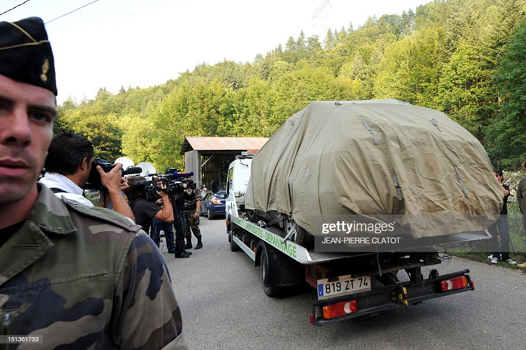 Photographers and cameramen shoot pictures while a tow truck, escorted by French gendarmes, is leaving with the car where three people were shot dead, on the 'Combe d'Ire' road, on September 6, 2012 in the French Alpine village of Chevaline. A four-year-old girl spent hours curled up under her mother's body and miraculously survived the deadly attack that left her father, mother and grandmother dead and her elder sister seriously injured, officials said.