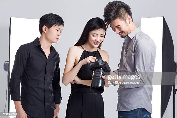 Photographers and female model looking pictures in camera together