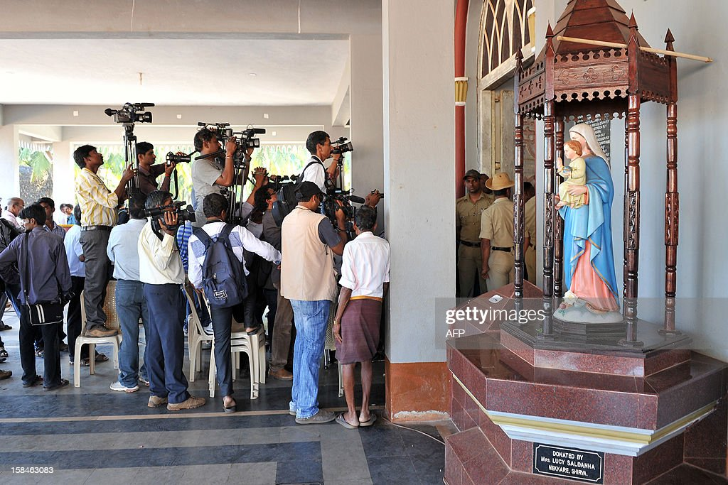 Photographers and journalists cover the funeral service for late nurse Jacintha Saldanha from outside The Shirve Church near Mangalore on December 17, 2012. About 2,000 mourners have packed a Catholic church in southwest India for the funeral of the nurse who was found hanged after taking a hoax call to the hospital treating Prince William's wife. Indian-born Jacintha Saldanha, 46, apparently committed suicide after answering the telephone call from Australian radio DJs to the hospital where the pregnant Duchess of Cambridge was admitted with acute morning sickness. AFP PHOTO/Manjunath KIRAN