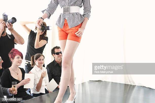 Photographers and spectators watching model on runway at fashion show
