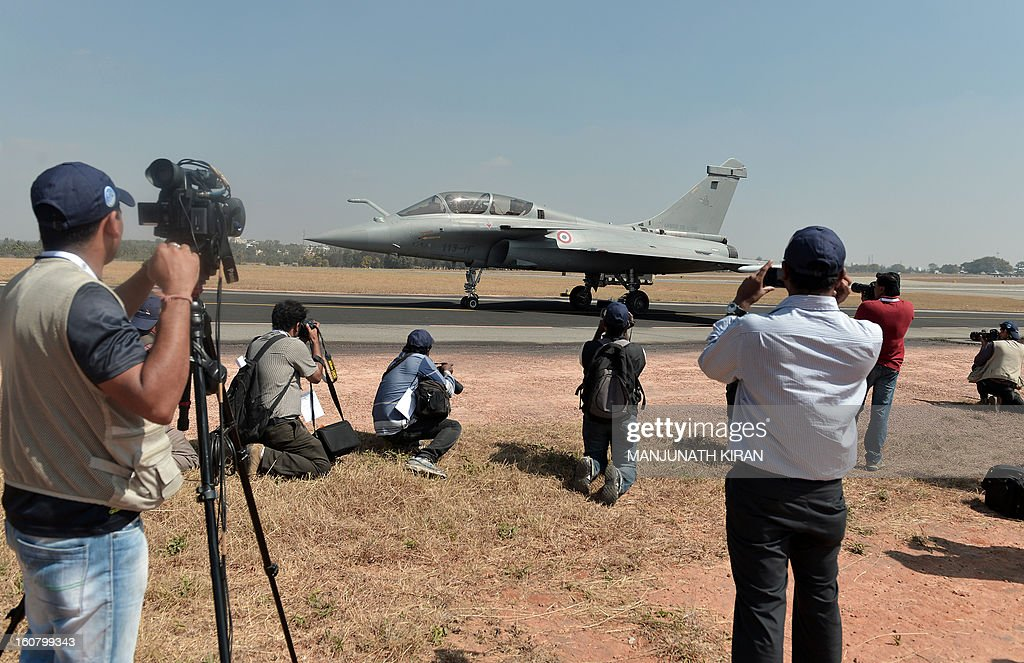 Photographers and videojournalists record footage of a French Rafale fighter taxiing during Aero India 2013 at the Yelahanka Air Force station in Bangalore on February 6, 2013. India, the world's leading importer of weaponry, opened one of Asia's biggest aviation trade shows Wednesday with Western suppliers eyeing lucrative deals and a Chinese delegation attending for the first time. AFP PHOTO/Manjunath KIRAN