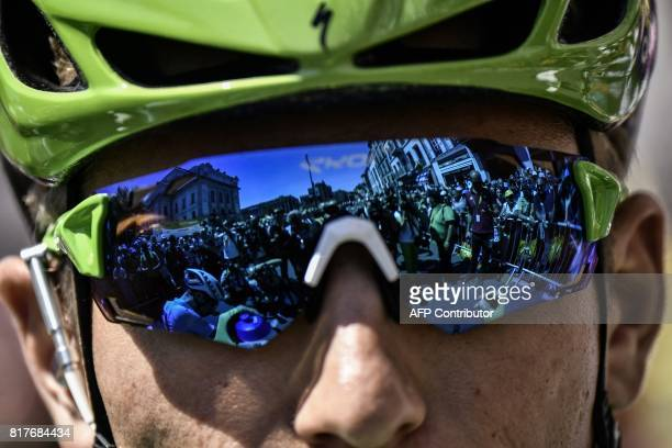 TOPSHOT Photographers are reflected in glasses of Germany's Marcel Kittel wearing the best sprinter's green jersey prior to the start of the 165 km...