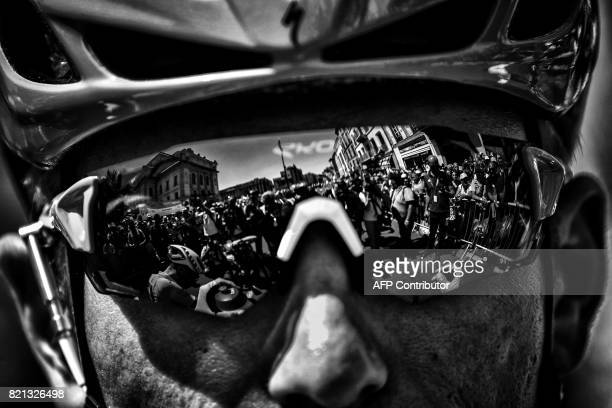 Photographers are reflected in glasses of Germany's Marcel Kittel wearing the best sprinter's green jersey prior to the start of the 165 km sixteenth...