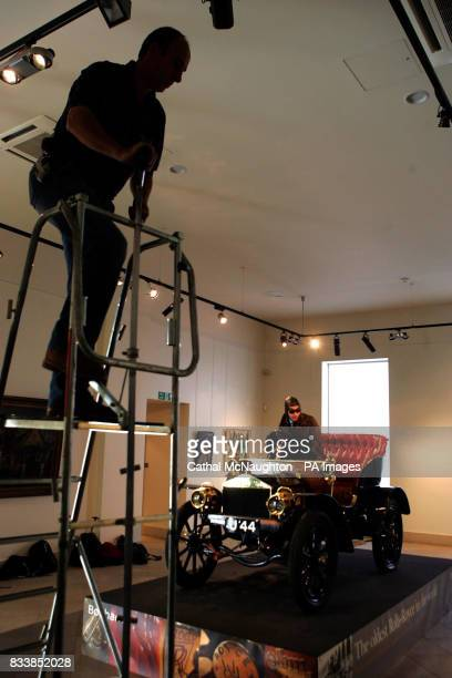 A photographers climbs a ladder to get a higher view of the worlds oldest surviving Rolls Royce car no 20154 built in 1904 on display at Bonhams in...