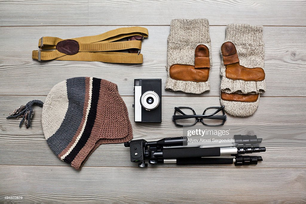 Photographer's equipment and clothing items arranged on floor : Stock Photo