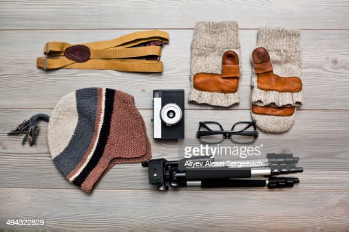 Photographer's equipment and clothing items arranged on floor
