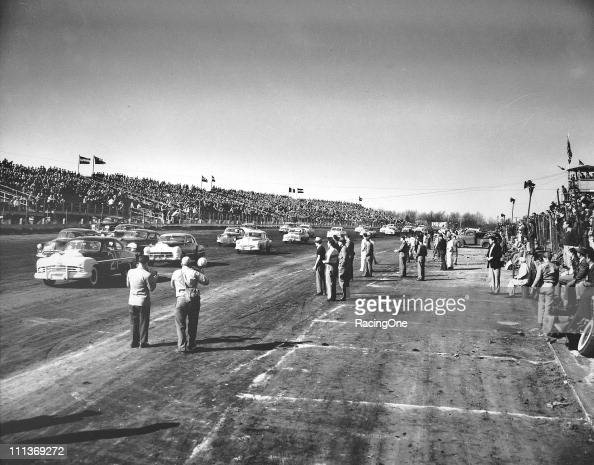 Photographers get bravely close to the action as Tim FlockÕs Lincoln leads the field during a NASCAR Cup race at Langhorne Speedway