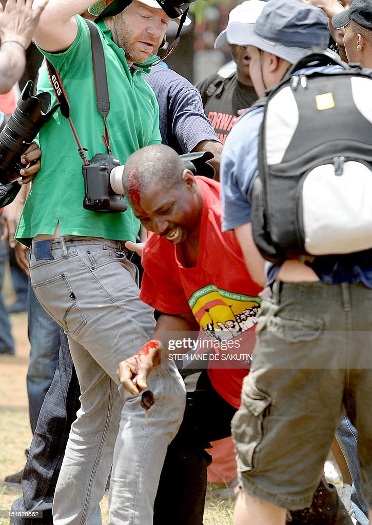 Photographers help an injured man (C) dressed in the red color of the Congress of South African Trade Unions (Cosatu) after he was beaten up by striking miners and as South African police officers fire rubber bullets, stun grenades and tear gas to disperse miners who were trying to prevent a rally organised by the Congress of South African Trade Unions (Cosatu) in Rustenburg, northwest of Johannesburg on October 27, 2012. Bullet casings littered the ground and a helicopter circled above, with police sirens howling, as the protesters were chased into the area surrounding the stadium. The clashes came a day after the National Union of Mineworkers (NUM) announced that it had reached a deal with the world's number one platinum producer Amplats to rehire 12,000 workers who were fired for a wildcat strike. Striking workers are disagree with the deal, which would signal a further winding down of a wave of wildcat strikes that have rocked platinum and gold mines since August. AFP PHOTO / STEPHANE DE SAKUTIN