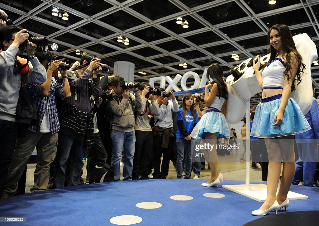 Photographers line up to take pictures of Sony Playstation promotion staff during the Asia Game Show (AGS) in Hong Kong on December 22, 2012. The AGS is highlighting products from the electronic gaming industry and runs from December 21 to 24. AFP PHOTO / Dale de la Rey