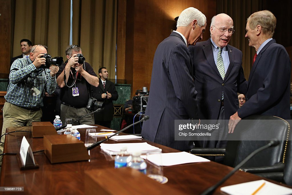Photographers make images of (L-R) Former Florida Gov. Charlie Crist, Senate Judiciary Committee Chairman Patrick Leahy (D-VT) and U.S. Sen. Bill Nelson (D-FL) talk before a committee hearing on voting rights at the Dirksen Senate Office Building on Capitol Hill December 19, 2012 in Washington, DC. According to the committee, the hearing focused on Americans' access to the voting booth 'and the continuing need for protections against efforts to limit or suppress voting.'