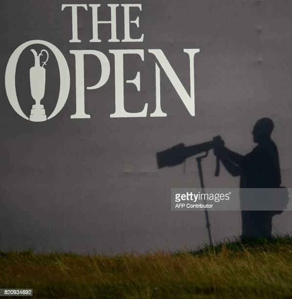 A photographer's shadow is seen beside the 18th green on day three of the Open Golf Championship at Royal Birkdale golf course near Southport in...