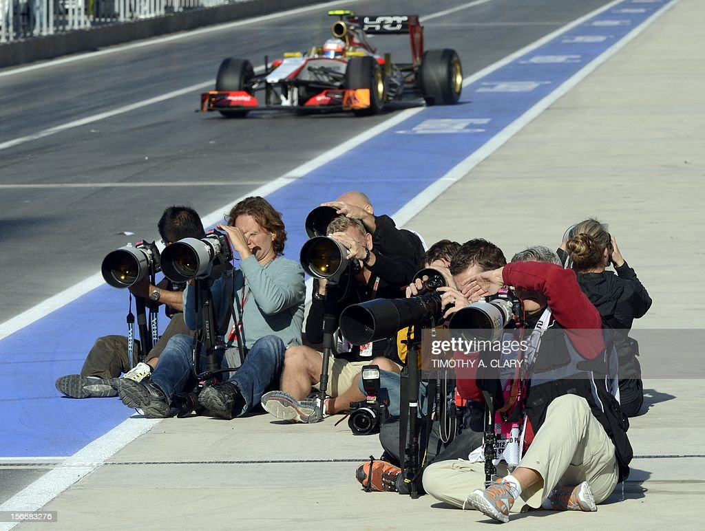 Photographers sit on the pit lane as a car pulls out of the pits during the third practice session for the United States Formula One Grand Prix at the Circuit of the Americas on November 17, 2012 in Austin, Texas.
