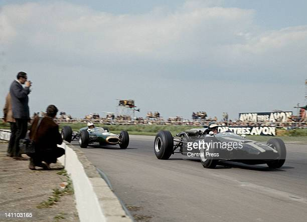 Photographers stand close to the track as Jochen Rindt of Austria drives the Cooper Car Company Cooper T81 Maserati V12 during the XVIII BRDC...