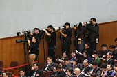 Photographers stand in line as they take photos during the 3rd plenary session of the third session of the12th National People's Congress at the...