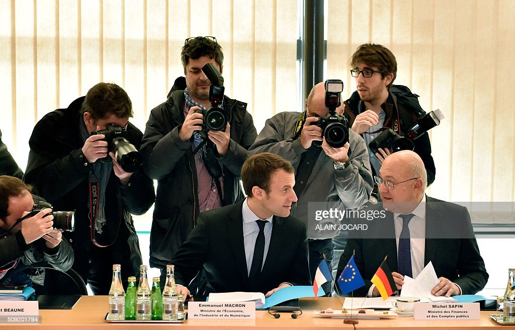 Photographers surround French Economy and Industry Minister Emmanuel Macron (L) as he sits next to French Finance Minister Michel Sapin (R), during the Franco-German Economic Council, on February 9, 2016, in Paris. / AFP / ALAIN JOCARD