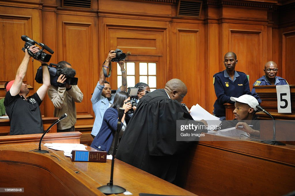 Photographers surround Xolile Mngeni in the Cape Town High Court on November 26, 2012 in Cape Town, South Africa. Mngeni was found guilty of robbery with aggravating circumstances, premeditated murder and illegal possession of a firearm and ammunition, after his involvement with the murder of Anni Dewani, allegedly plotted by her British husband Shrien Dewani.