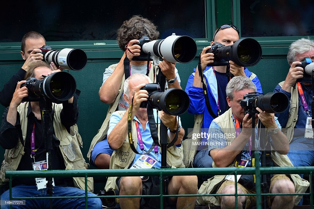 Photographers take images during the women's singles tennis first round match between Poland's Agnieszka Radwanska and Julia Goerges of Germany at The All England Tennis Club in Wimbledon, southwest London on July 29, 2012, for The 2012 London Olympic Games.