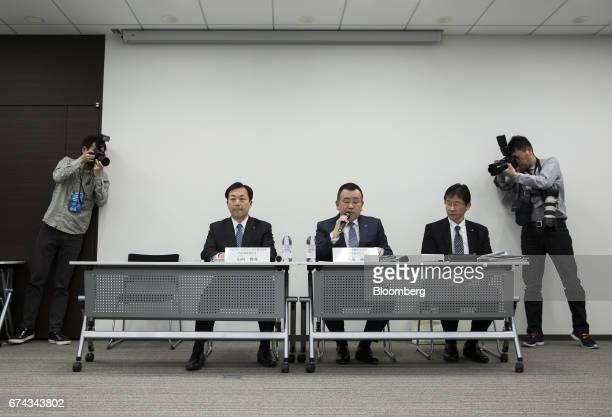 Photographers take photographs of Masaki Yamauchi president of Yamato Holdings Co left and Yutaka Nagao president of Yamato Transport Co center...
