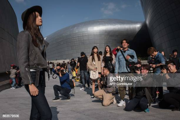 Photographers take photos of a model during Seoul fashion week at Dongdaemun Design Plaza in Seoul on October 20 2017 For Seoul's flamboyant...