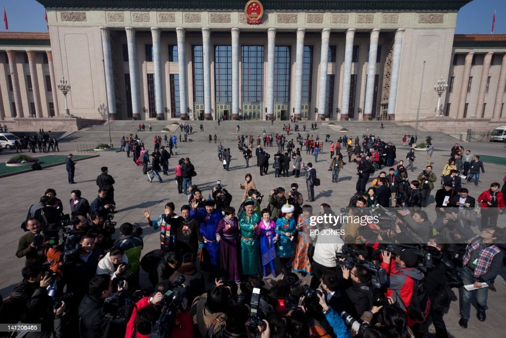 Photographers take photos of delegates representing ethnic minorities following the last day of the Chinese People's Political Consultative Conference (CPPCC) during the National People's Congress (NPC) in Beijing on March 13, 2012. The 2012 NPC session is the last before a handover of power that begins later this year, and leaders are anxious to ensure the world's second-largest economy grows at a steady pace while keeping a lid on social unrest. AFP PHOTO / Ed Jones