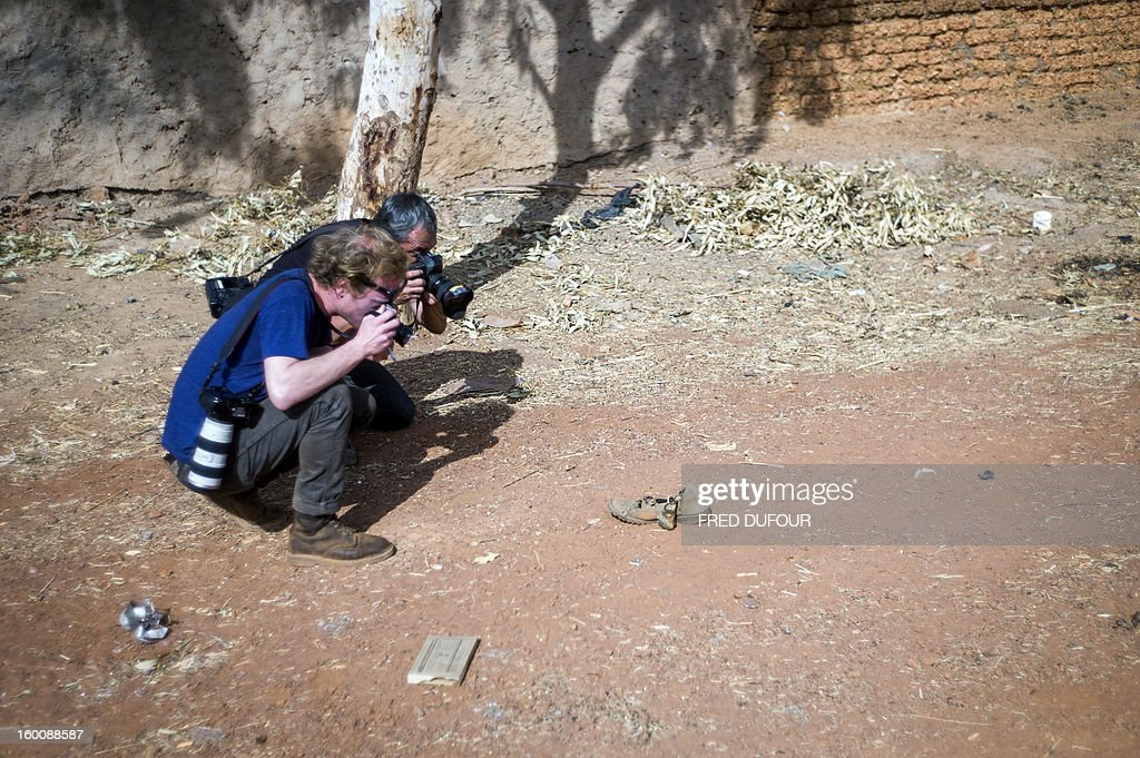 Photographers take pictures a of a shoe lying on the street of a destroyed area of Konna on January 26, 2013. French-led forces today wrested control of the airport at the Islamist stronghold of Gao, 1,200 kilometres (750 miles) northeast of the Mali capital Bamako, a security source said.