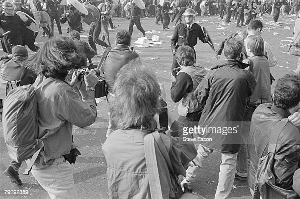 Photographers take pictures as police and demonstrators clash in Trafalgar Square during rioting which arose from a demonstration against the Poll...