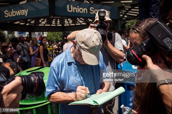 Photographers take pictures of a man signing a petition supporting former New York Gov Eliot Spitzer to run for comptroller of New York City on July...