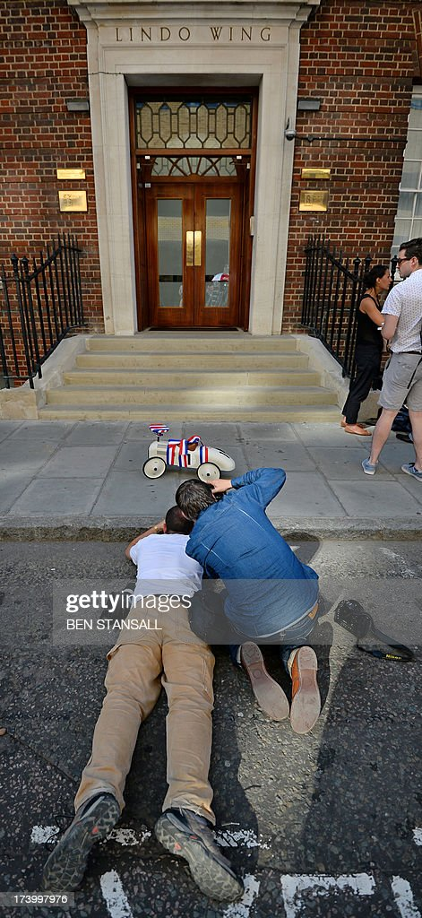 Photographers take pictures of a toy car delivered as a gift to the Lindo Wing of St Mary's Hospital in London, on July 19, 2013, where Prince William and his wife Catherine's baby is expected to be born. The long wait for the birth of Britain's royal baby is record business for bookmakers, as punters worldwide bet on a girl called Alexandra to be born any day now.