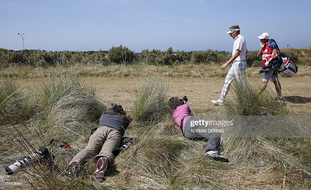 Photographers take pictures of England's Ian Poulter as he walks across a fairway during the third round of the 2013 British Open Golf Championship at Muirfield golf course at Gullane in Scotland on July 20, 2013.