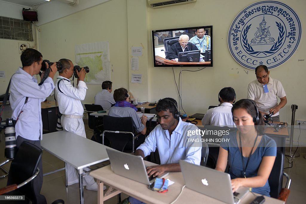 Photographers (L) take pictures of former Cambodian Khmer Rouge leader 'Brother Number Two' Nuon Chea (top C) on a livefeed video during the trial of former Khmer Rouge leaders at the Extraordinary Chamber in the Courts of Cambodia (ECCC) in Phnom Penh on October 31, 2013. Two former Khmer Rouge leaders make their closing statements on October 31 in the landmark trial against surviving members of the murderous regime at Cambodia's UN-backed war crimes court. AFP PHOTO/ TANG CHHIN SOTHY