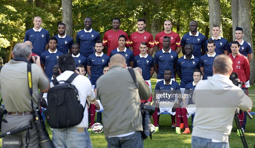 Photographers take pictures of (from L-Up) France's defender Jeremy Mathieu, forward Alexandre Lacazette, midfielder Moussa Sissoko, goalkeeper Steve Mandanda, goalkeeper Hugo Lloris, goalkeeper Stephane Ruffier, defender Eliaquim Mangala, defender Lucas Digne and midfielder Remy Cabella, (center-from L) assistant coach Guy Stephan, forward Loic Remy, midfielder Rio Mavuba, defender Mathieu Debuchy, defender Raphael Varane, forward Antoine Griezmann, midfielder Paul Pogba, defender Bakary Sagna, midfielder Morgan Schneiderlin and goalkeeper coach Franck Raviot, (down-from L) France's defender Mamadou Sakho, midfielder Yohan Cabaye, forward Karim Benzema, head coach Didier Deschamps, midfielder Blaise Matuidi, midfielder Mathieu Valbuena and defender Patrice Evra pose in Clairefontaine-en-Yvelines on September 2, 2014. France will play a friendly football match against Spain ahead of the Euro 2016 qualifiers.