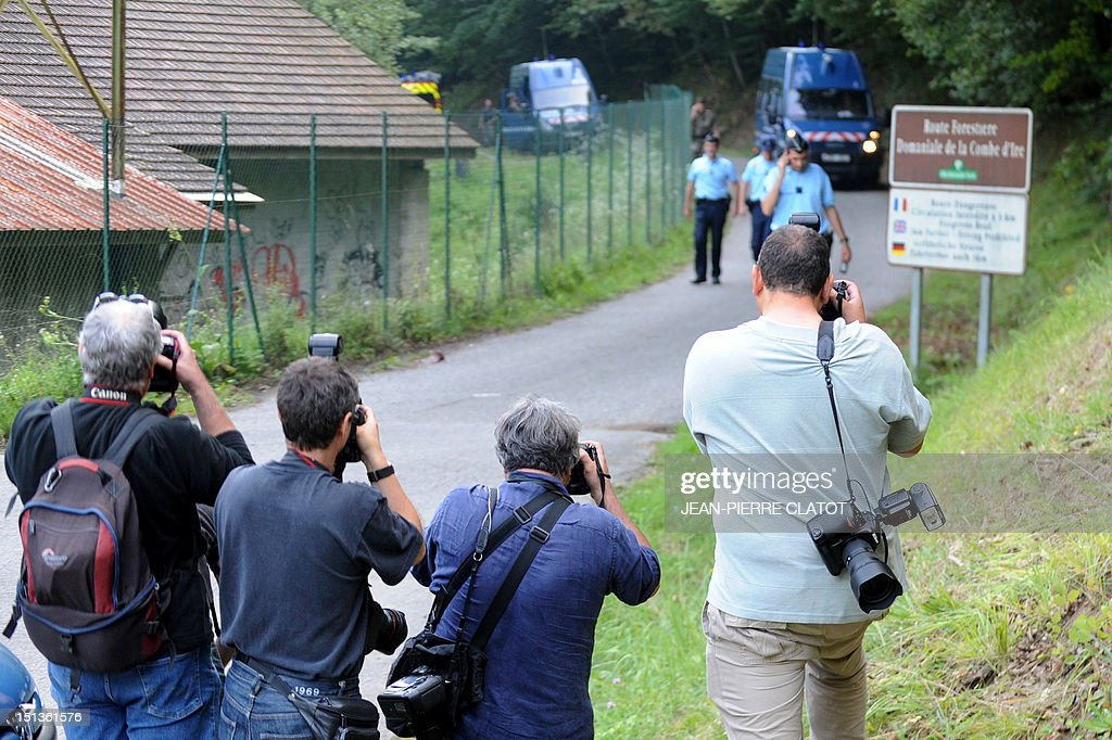 Photographers take pictures of French gendarmes on the 'Combe d'Ire' road, on September 6, 2012 in the French Alpine village of Chevaline, as they were escorting a tow truck with the car where four people were shot dead. A four-year-old girl spent hours curled up under her mother's body and miraculously survived the deadly attack that left her father, mother and grandmother dead and her elder sister seriously injured, officials said.