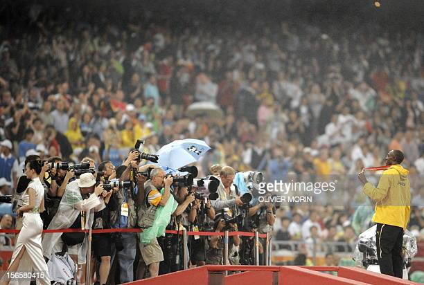 Photographers take pictures of Jamaica's Usain Bolt as he poses on the podium with his gold medal during the men's 200m medal ceremony at the 'Bird's...