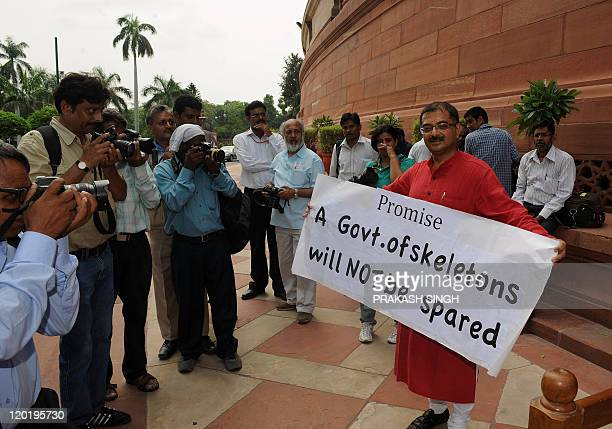 Photographers take pictures of Parliament member Tarun Vijay who poses with a poster before the opening of Parliaments monsoon session in New Delhi...