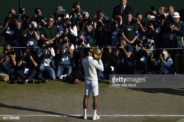 Photographers take pictures of Serbia's Novak Djokovic as he kisses the winner's trophy after beating Switzerland's Roger Federer in the men's...
