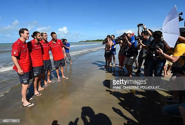 Photographers take pictures of Switzerland's midfielder Valon Behrami defender Stephan Lichtsteiner and forward Haris Seferovic on the beach of La...