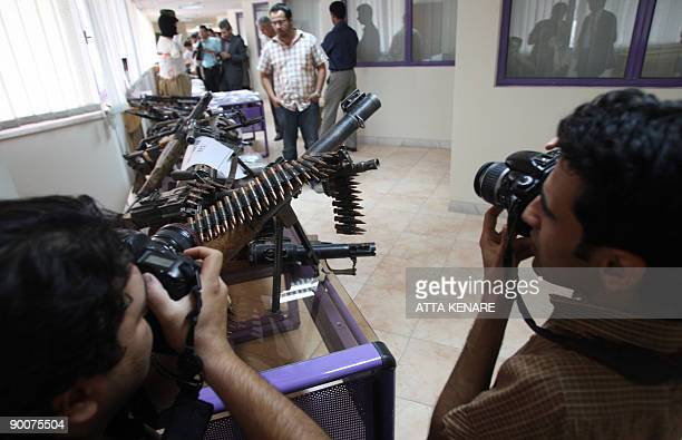 Photographers take pictures of weapons allegedly confiscated from the Jundallah Sunni rebel group at a government building in Iran�s restive...