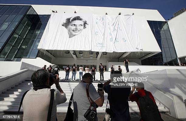 Photographers take pictures of workers setting up the official poster of the 68th Cannes' film festival showing the Swedish actress Ingrid Bergman on...