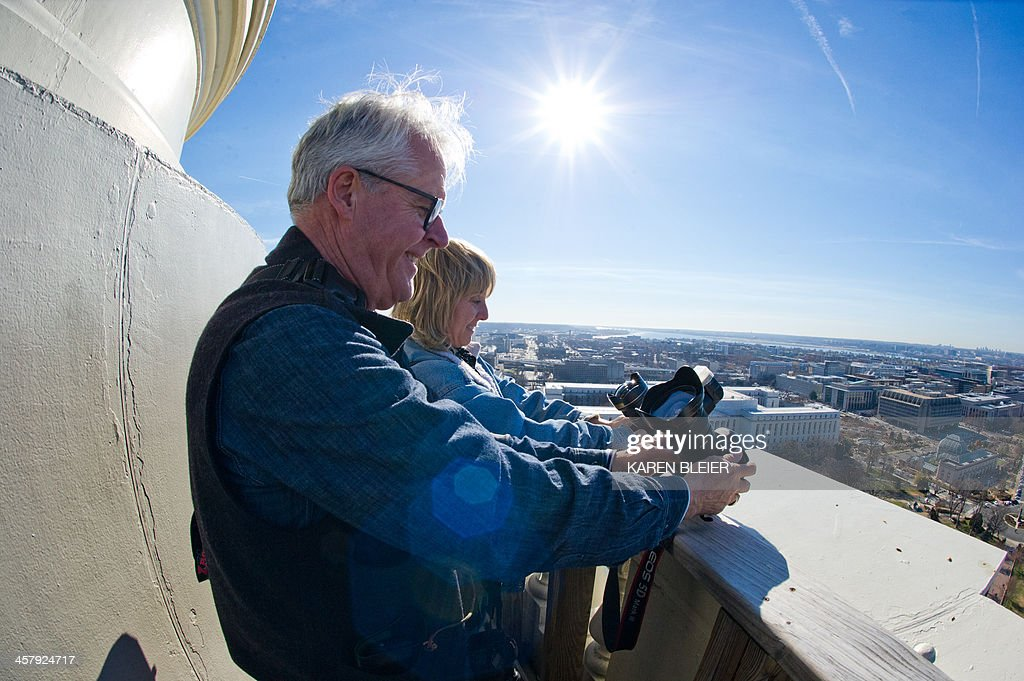 Photographers take selfies from the top of the US Capitol dome during a tour of the dome December 19, 2013 in Washington, DC. The Dome has not undergone a complete restoration since 1959-1960 and due to age and weather is now plagued by more than 1,000 cracks and deficiencies. The Architect of the Capitol began in November, a multi-year project to repair these deficiencies, restoring the Dome to its original, inspiring splendor. AFP PHOTO / Karen BLEIER