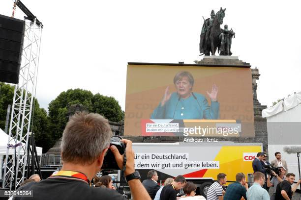 A photographers takes pictures of a video wall showing German Chancellor and head of the German Christian Democrats Angela Merkel speaking on stage...