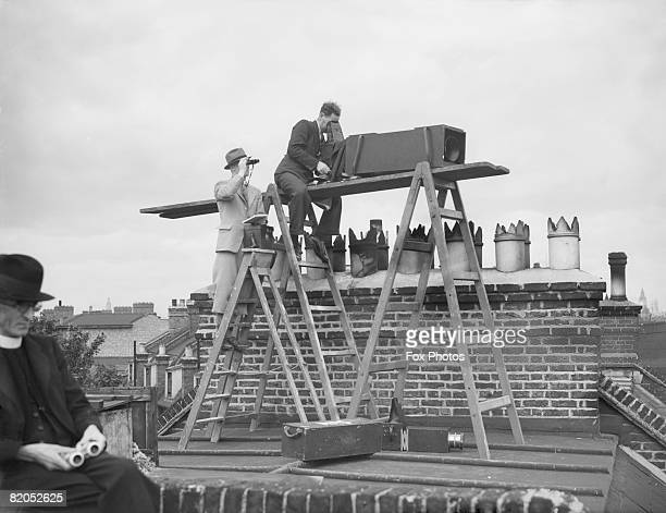 Photographers use a longfocus camera from a rooftop at the Oval to capture images of the test match 20th August 1938 Behind the man with the camera...