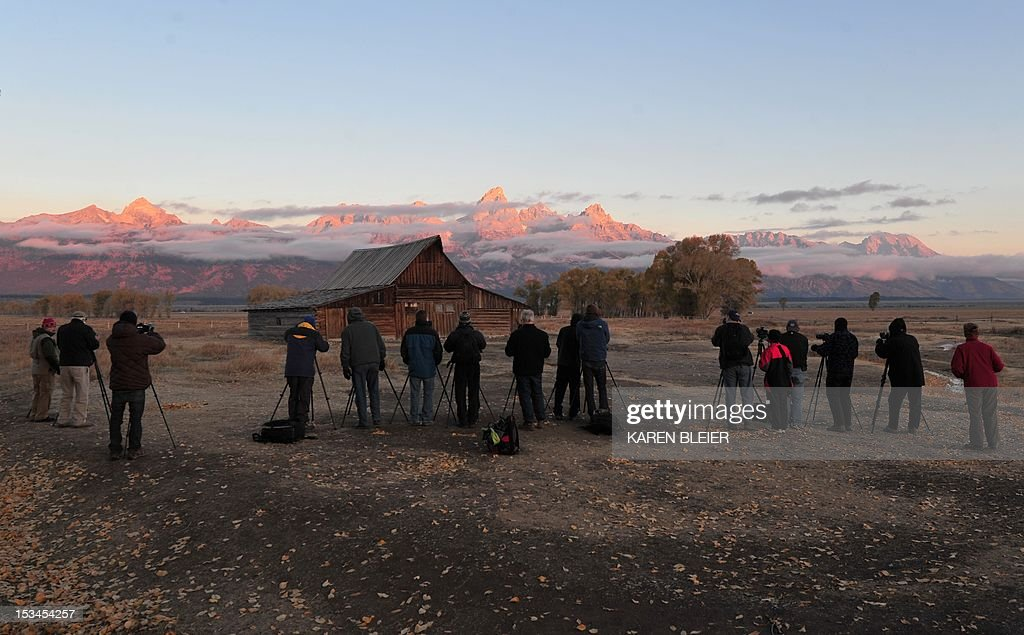 Photographers wait in freezing temperatures to capture the morning Sun as it hits the tips of the Grand Tetons at Moulton barn October 5, 2012 in the Grand Teton National Park in Wyoming. Grand Teton National Park is located in northwestern Wyoming. Approximately 310,000 acres (130,000 ha) in size, the park includes the major peaks of the 40-mile (64 km) long Teton Range as well as most of the northern sections of the valley known as Jackson Hole. AFP PHOTO/Karen BLEIER