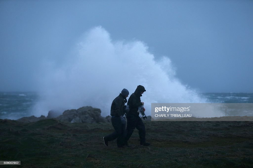 Photographers walk in front of a breaking wave in the harbour in Auderville, northwestern France, on February 8, 2016, as strong winds hit the region. Winds of over 130 kh/h were recorded in the region where 16 departments have been placed under alert for wind and flooding waves. / AFP / CHARLY TRIBALLEAU