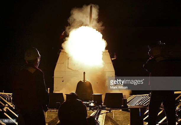 Photographers watch as a Tomahawk cruise missile launches toward Iraq from the deck of the AEGIS guided missile cruiser USS San Jacinto March 21 2003...