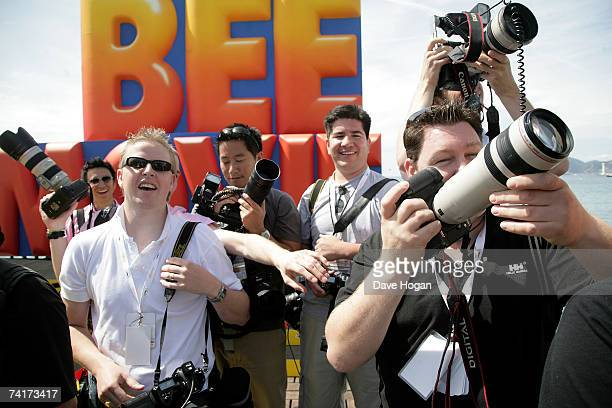 Photographers watch as actor Jerry Seinfeld prepares to slide down on a wire from the Carlton Hotel dressed as a bee to promote the film 'Bee Movie'...