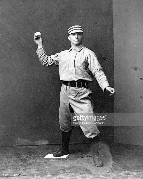 A photographic portrait of Tommy McCarthy wearing a Philadelphia Quakers uniform in the photograph he is posing as though he is about to throw a...