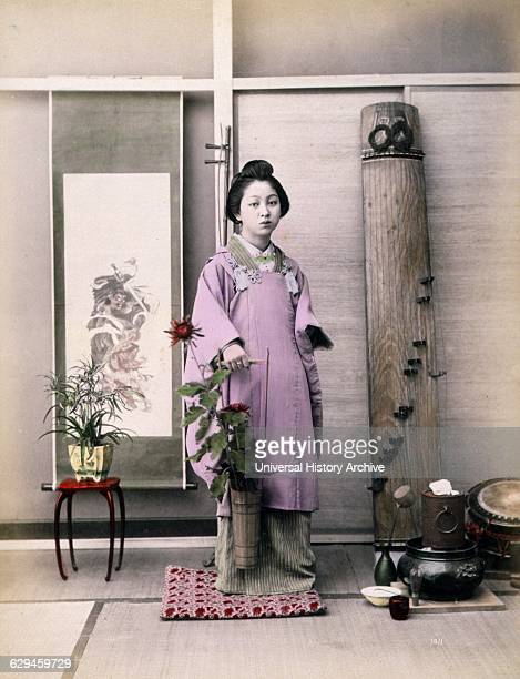 albumen hand coloured with watercolour Photograph shows a portrait of a young woman fulllength standing facing front holding a small longhandled...